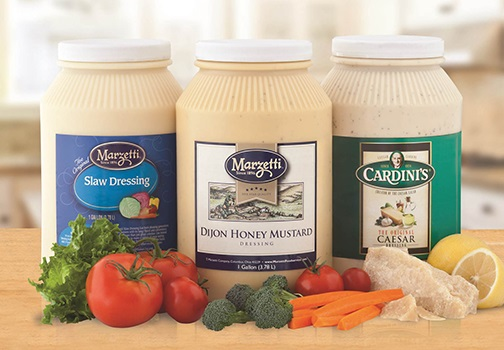 Wood tabletop grouping of three Foodservice gallon sized containers of Marzetti® brand Slaw Dressing, Marzetti brand Dijon Honey Mustard Dressing and Cardini's® brand Caesar dressing. Food props of lettuce, tomato, broccoli, carrots cheese and lemon.
