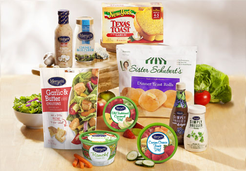 Wood tabletop with a large grouping of several packaged items, including: Marzetti® brand croutons, salad dressing and dips; New York BRAND® Bakery Texas Toast; and Sister Schubert's® Dinner Yeast Rolls. Food prop accents of vegetables and salad greens.