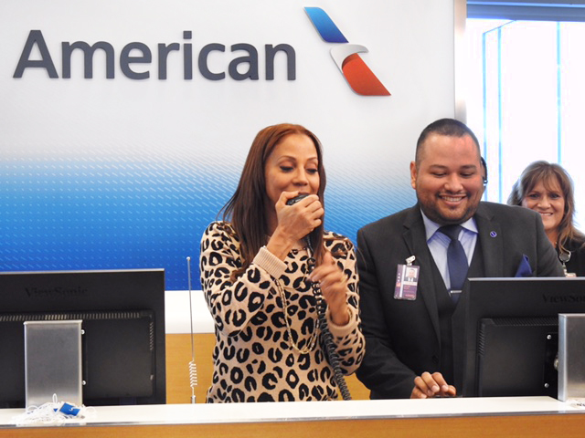 Actress Holly Robinson Peete makes an announcement with Customer Service Coordinator Ralph Galvan at the It's Cool to Fly event at LAX.