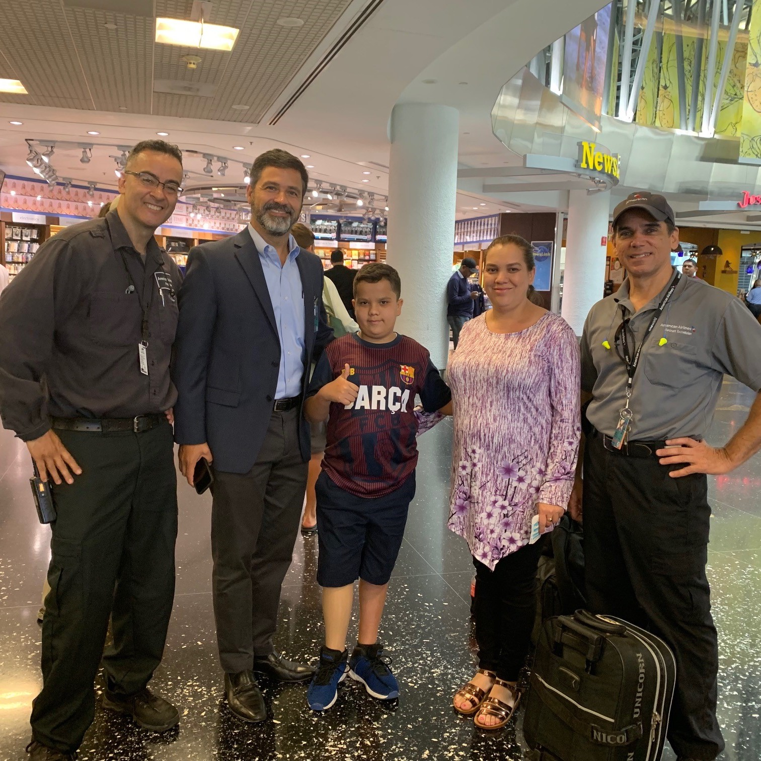 From left, CEBRG Miami President Phil Revollo, Vice President of MIA Hub Operations Juan Carlos Liscano and CEBRG Miami Vice President John Malik (far right) visit with Emanuel and his mother, Idalia, at the airport.