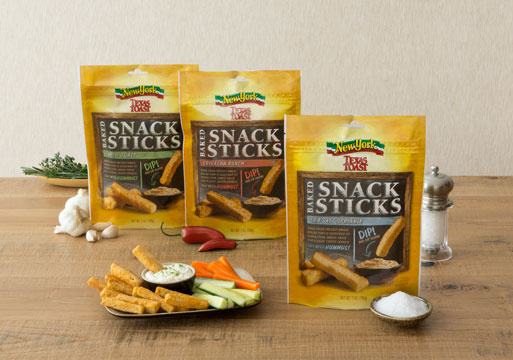 Wood tabletop with three packages side by side of New York BRAND® Bakery Snack sticks. A bowl of carrot and celery sticks, with the Snack Sticks and a small bowl of dip.