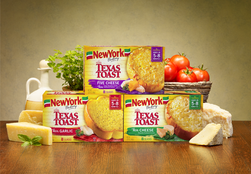 Wood tabletop with a grouping of three varieties of New York BRAND® Bakery Texas Toast packaged items: Five Cheese; Garlic; and Cheese. Prop accents of a basket of tomatoes, cheese wedges and fresh herbs.