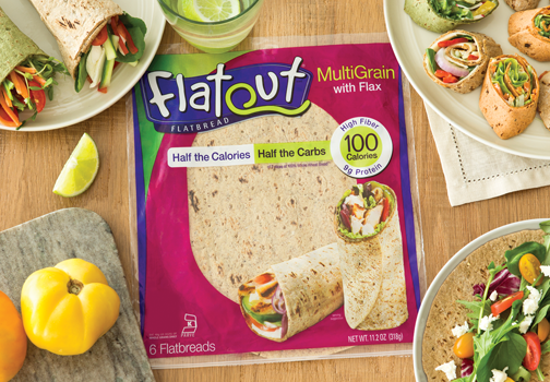 Wood tabletop with a packaged bag of Flatout® Multigrain flatbread, surrounded by platters of rolled veggie wraps and a cutting board with yellow and orange Bell peppers along with a bowl containing an assortment of vegetables.