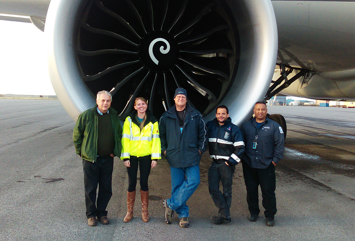 The ground crew stand in front of a jet engine.