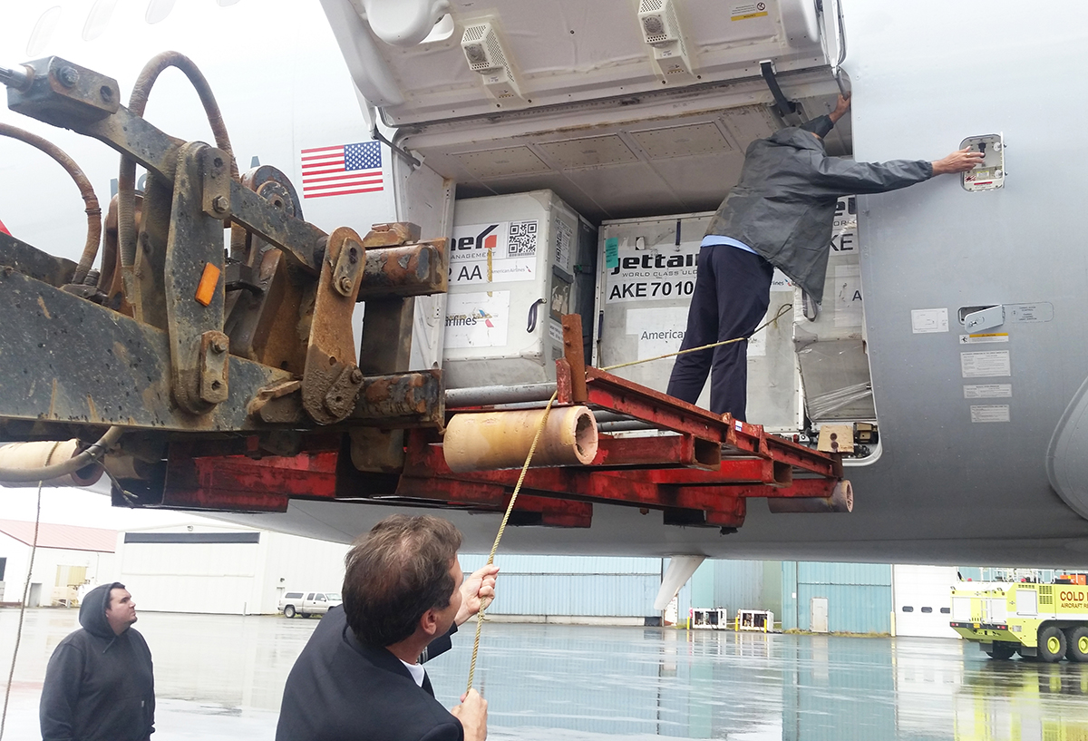 Ground crew members work to secure cargo.