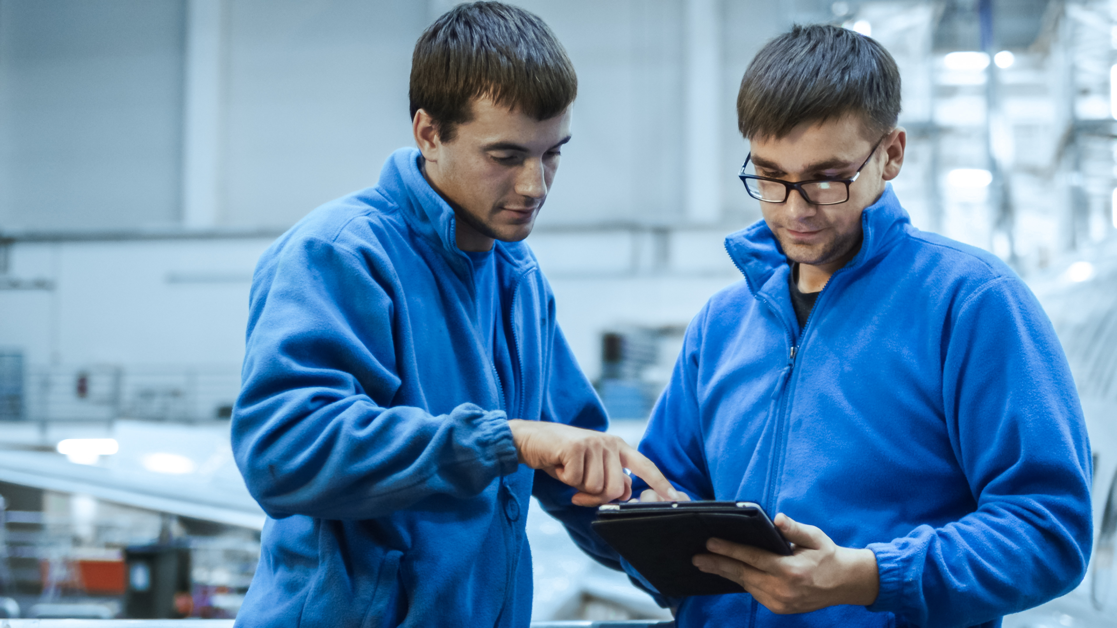 Two Men in Blue Reviewing Paperwork on a Tablet