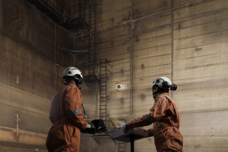 Two staff members guide a confined space UAS up a wall